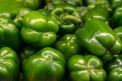 Paprikas verts sur un compteur dans le supermarché Un grand nombre de poivrons verts dans une pile Photos stock
