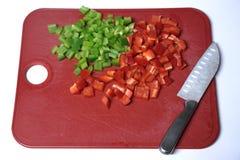 Paprikas y Chef& x27; cuchillo de s en tabla de cortar Foto de archivo libre de regalías