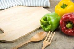 Paprikas y utensilios de la cocina sobre la tabla de madera fotografía de archivo libre de regalías
