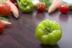 Paprikorna på en tabell på bakgrunden av grönsaker Nya tomater och peppar på en träbrun tabell Royaltyfria Bilder