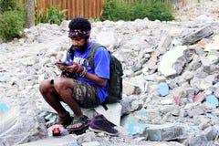 Papua man som ut kontrollerar hans mobiltelefon Arkivbilder