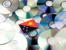 Papua-Neu-Guinea Flagge auf den CD- und DVD-Stapel lokalisiert auf Whit Lizenzfreies Stockfoto