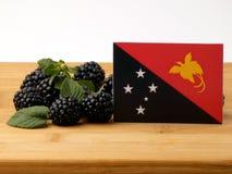 Papua-Neu-Guinea Flagge auf einer Holzverkleidung mit Brombeeren-isolat Stockfotografie