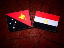 Papua-Neu-Guinea Flagge mit ägyptischer Flagge auf einem Baumstumpfisolat Lizenzfreie Stockfotografie