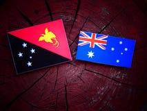 Papua-Neu-Guinea Flagge mit australischer Flagge auf einem Baumstumpf lokalisiert Lizenzfreies Stockbild