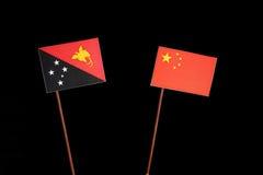 Papua-Neu-Guinea Flagge mit chinesischer Flagge auf Schwarzem Stockbild