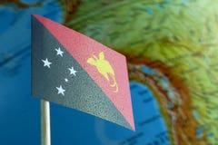 Papua-Neu-Guinea Flagge mit einer Kugelkarte als Hintergrund stockfotografie