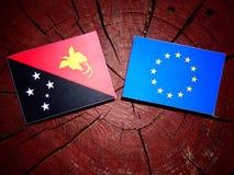 Papua-Neu-Guinea Flagge mit EU-Flagge auf einem Baumstumpf lokalisiert Lizenzfreie Stockfotos