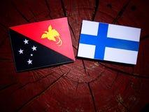 Papua-Neu-Guinea Flagge mit finnischer Flagge auf einem Baumstumpf lokalisiert Stockbilder