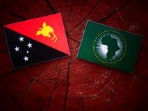 Papua-Neu-Guinea Flagge mit Flagge der Afrikanischen Union auf einem Baumstumpf ist Lizenzfreie Stockfotos