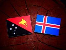 Papua-Neu-Guinea Flagge mit isländischer Flagge auf einem Baumstumpf isolat Stockfotografie