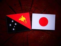 Papua-Neu-Guinea Flagge mit japanischer Flagge auf einem Baumstumpf lokalisiert Lizenzfreie Stockbilder