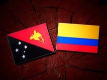 Papua-Neu-Guinea Flagge mit kolumbianischer Flagge auf einem Baumstumpf isolat Lizenzfreie Stockfotografie