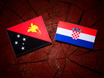 Papua-Neu-Guinea Flagge mit kroatischer Flagge auf einem Baumstumpfisolat Stockbild