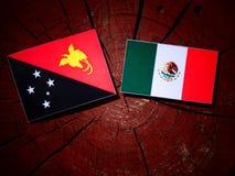 Papua-Neu-Guinea Flagge mit mexikanischer Flagge auf einem Baumstumpf lokalisiert Lizenzfreie Stockfotografie