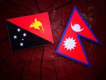 Papua-Neu-Guinea Flagge mit Nepaliflagge auf einem Baumstumpf lokalisiert Stockfotos