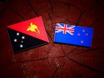 Papua-Neu-Guinea Flagge mit Neuseeland-Flagge auf einem Baumstumpfisolator Stockbilder