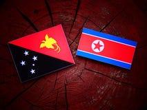 Papua-Neu-Guinea Flagge mit nordkoreanischer Flagge auf einem Baumstumpf Lizenzfreie Stockbilder