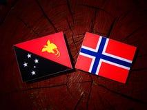 Papua-Neu-Guinea Flagge mit norwegischer Flagge auf einem Baumstumpf isolat Stockbild