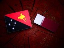 Papua-Neu-Guinea Flagge mit Qatari-Flagge auf einem Baumstumpf lokalisiert Lizenzfreies Stockfoto
