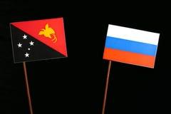 Papua-Neu-Guinea Flagge mit russischer Flagge auf Schwarzem Lizenzfreie Stockfotografie