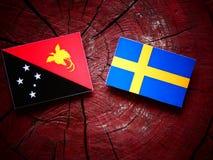 Papua-Neu-Guinea Flagge mit schwedischer Flagge auf einem Baumstumpf Stockfotos