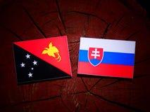 Papua-Neu-Guinea Flagge mit slowakischer Flagge auf einem Baumstumpf isolat Lizenzfreie Stockbilder