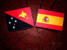 Papua-Neu-Guinea Flagge mit spanischer Flagge auf einem Baumstumpf Stockfoto