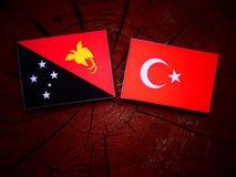 Papua-Neu-Guinea Flagge mit türkischer Flagge auf einem Baumstumpf Lizenzfreies Stockfoto