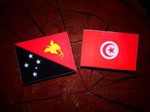 Papua-Neu-Guinea Flagge mit tunesischer Flagge auf einem Baumstumpfisolat Lizenzfreies Stockfoto