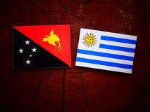 Papua-Neu-Guinea Flagge mit Uruguaian-Flagge auf einem Baumstumpf isolat Lizenzfreie Stockfotografie