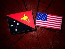 Papua-Neu-Guinea Flagge mit USA-Flagge auf einem Baumstumpf Lizenzfreies Stockfoto