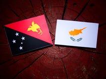 Papua-Neu-Guinea Flagge mit zypriotischer Flagge auf einem Baumstumpf lokalisiert Lizenzfreie Stockbilder