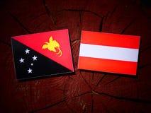 Papua New Guinea flag with Austrian flag on a tree stump isolate Royalty Free Stock Photos