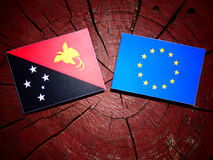 Papua New Guinea flag with EU flag on a tree stump isolated. Papua New Guinea flag with EU flag on a tree stump Royalty Free Stock Photos