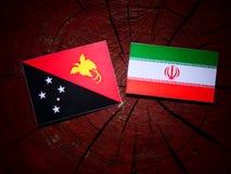 Papua New Guinea flag with Iranian flag on a tree stump isolated. Papua New Guinea flag with Iranian flag on a tree stump Stock Photos