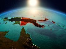 Papua New Guinea in sunrise from orbit. Sunrise above Papua New Guinea highlighted in red on model of planet Earth in space with visible country borders. 3D Stock Images