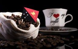 Papua Nya Guinea flagga i en påse med kaffebönor på svart Arkivfoto