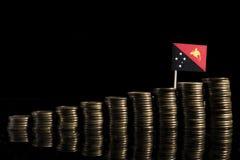 Papua Nya Guinea flagga med lotten av mynt som isoleras på svart backgr Royaltyfri Bild