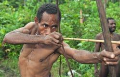 Papuan从弓的射击箭头 自然绿色密林背景 免版税库存图片