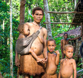 Papuan family. Man, woman and little children of Korowai tribe Stock Images