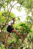 Papuan girl climbing mango tree royalty free stock photography