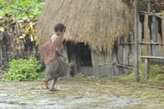 Papuan girl from Dani tribe  hurries to hide from a rain under a roof. Royalty Free Stock Photography