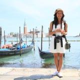 Papuan girl in front of gondolas in harbor in Venice Stock Image