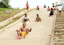 Papuan kids sledding on road Royalty Free Stock Photography