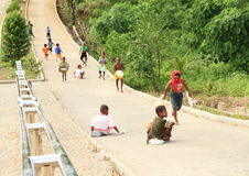 Papuan kids sledding on road Stock Photos
