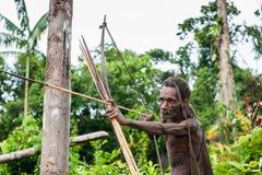 The Papuan from a Korowai tribe aims for shoots an archer. Korowai kombai (Kolufo) with bow and arrows Royalty Free Stock Photos