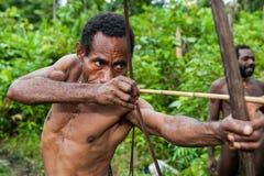 The Papuan from a Korowai tribe aims for shoots an archer. Korowai kombai (Kolufo) with bow and arrows Royalty Free Stock Photography