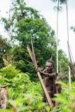 The Papuan from a Korowai tribe aims for shoots an archer. Korowai kombai (Kolufo) with bow and arrows Stock Photo