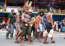 Papuan men with ukulele from Wamena. Papuan man with musical instruments ukulele clothed in traditional clothes and body paintings and feather headdress from Stock Images